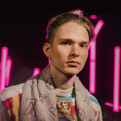 Vaaleahiuksinen nuori mies katsoo suoraan kameraan vakavalla ilmeellä pinkkien neonvalotolppien edessä.