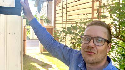 En man med glasögon står med handen mot en halvbyggd träfasad.