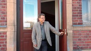 En man står vid ytterdörren till en gammal röd tegelbyggnad.
