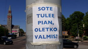"Ett papper med texten ""Sote tulee, oletko valmis?"" fasttejpad på en lyktstolpe i Helsingfors."