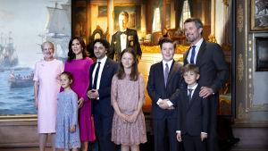 Familj poserar framför ett stort porträtt