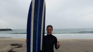 Malin Kivelä står med surfbräda och en vid ocean i grådaskigt ljus i bakgrunden. Bär våtdräkt och ler. Tummen uppe.