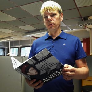 Petri P. Pentikäinen pitää käsissään uunituoretta kirjaansa Kalvitsan kylästä.