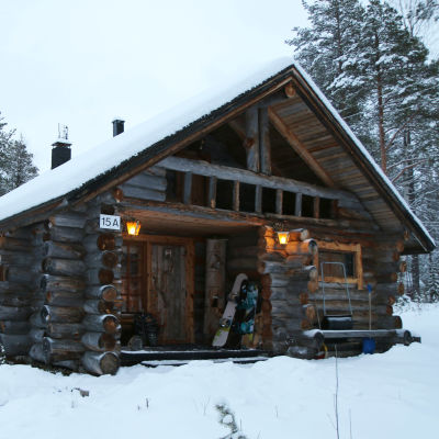 Snötäckt timmerstuga på Levi i Kittilä i Lappland.