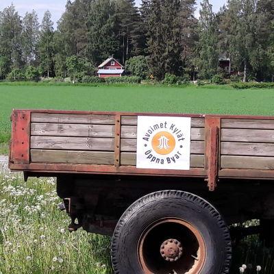 Mainoskyltti traktorin peräkärryn kyljessä.