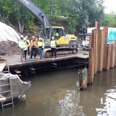 Flera personer står på en brokonstruktion på en byggarbetsplats vid vatten. I bakgrunden en grävmaskin.