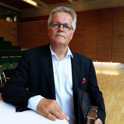 Tidigare chefredaktör Torbjörn Kevin står vid ett bord i ett auditorium med en mapp under armen.