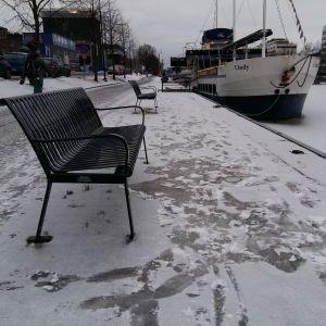 Någon har halkat omkull och gjort spår i snön vid en parkbänk på östra åstranden i Åbo.