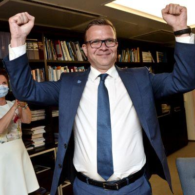 Petteri Orpo, en man i kostym och glasögon pumpar sina händer i luften.