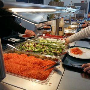 Skolmatens salladsbord med riven morot, sallad, gurka och grynost.