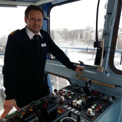Silja Serenades kapten Niklas Nordlund står i fönstret på kommandobryggan framför en rad spakar.
