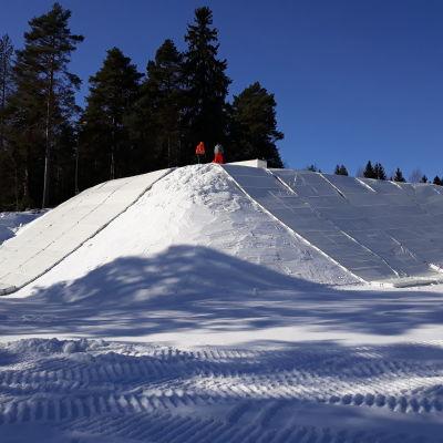 Korkean lumivaraston päällä seisoo kaksi ihmistä.