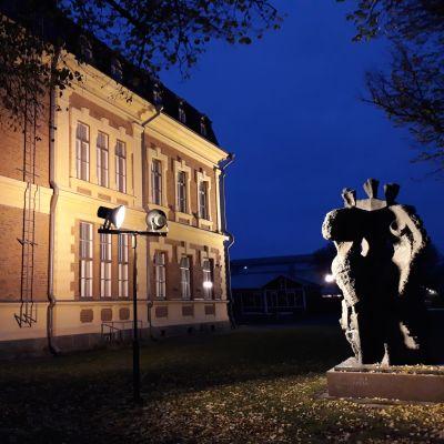 Valonheittimet valaisevat Joensuun taidemuseon päätyä ja Maiju Lassilan patsasta syksyn yössä.