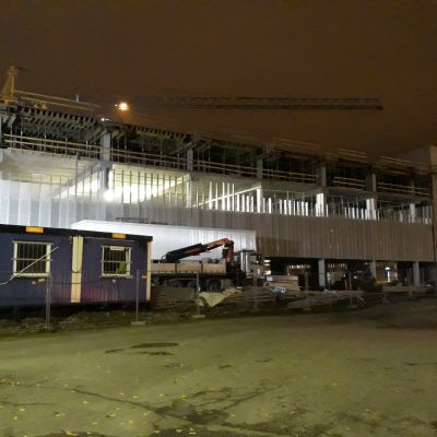 Harjakorkeudessa oleva aseman pysäköintitalo yövalaistuksessa.