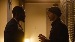 Francis och Jere inbegripna i livligt samtal i dunkelt rum.