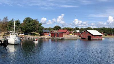 Borstö med röda båthus intill förbindelsebåtsbryggan.