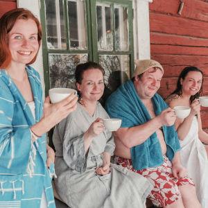 Kolme naista ja yksi mies vilvoittelevat kuistilla löylyjen jälkeen teekupit käsissään ja hymyilevät iloisesti.