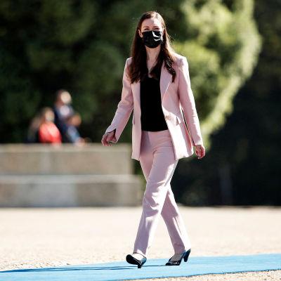 Statsminister Sanna Marin går utomhus iklädd en rosa kostym.