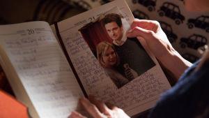 Närbild av Bridgets uppslagna dagbok där ett foto av henne och Mark Darcy syns