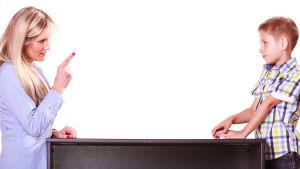En kvinna och en pojke vid ett bord. Kvinnan har fingret i luften och pojken lyssnar på henne.
