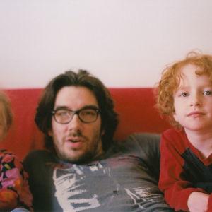 Isä ja kaksi lasta istuvat sohvalla.