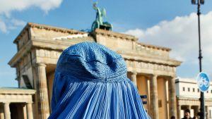 Kvinna iklädd burka vid Brandenburger Tor i Berlin.