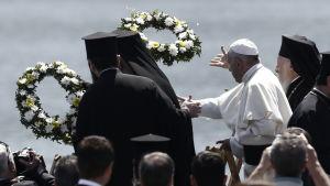 Påve Franciskus och Patriark Bartholomeus I (båda till höger) kastar blomkransar i havet i Mytiliene-hamnen