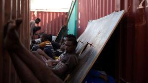 Flyktingar väntar på att transporteras till ett libyskt interneringsläger
