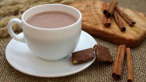 En kopp kakao, med två chokladbitar på fatet. På bordet ligger några kanelstänger.