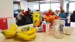 På ett bord står frukt, saft, en tom glasburk och små chokladpåskägg i en påse. Bakom matvarorna syns flera människor som sitter runt ett långt bord.