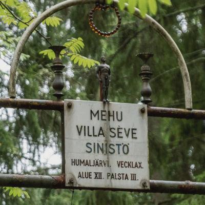 """Portkonstruktion med en skylt med texten """"Mehu Villa Seve Sinistö, Humaljärvi, Vecklax, Alue 12, Palsta 3""""."""