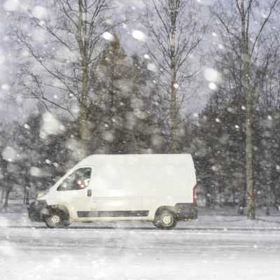 Auto ajaa lumisateessa Oulussa.
