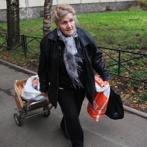 En äldre dam bär på matkassar