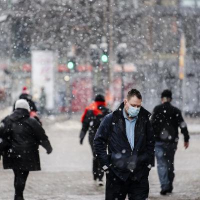 Människor i munskydd går i Helsingfors medan det snöar.