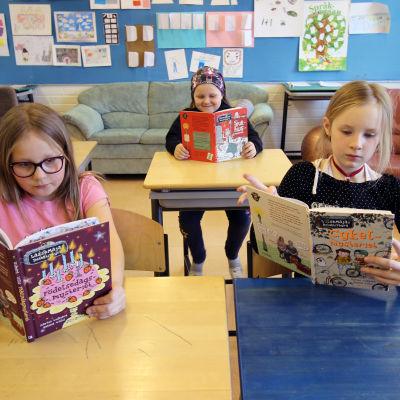 Aada Johansson, Peppi Johansson och Maya Ikonen sitter och läser i sitt klassrum i Svenska skolan i Varkaus.