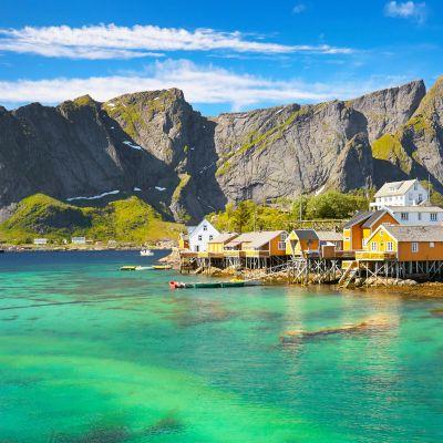 En fjord med turkos vatten och ett stort berg. Några små hus i gult syns på bilden.
