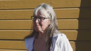 Airi Ruohonen taustallaan vaaleanruskea puutalon seinä.