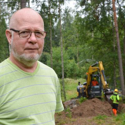 Rabbe Forsblom i t-shirt, i bakgrunden ser man en grävmaskin och arbetare