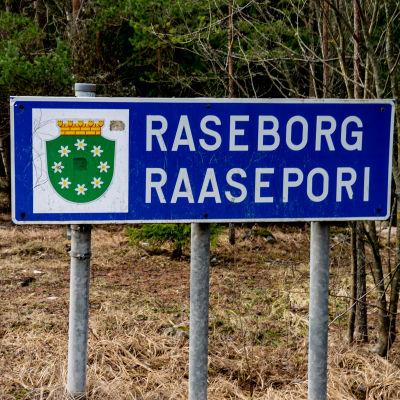En skylt, där det står Raseborg, står i terrängen vid kommungränsen.