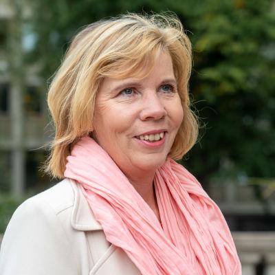 Justitieminister Anna-Maja Henriksson intervjuas. Hon är iklädd en rosa skarf och ljus jacka.