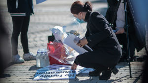 En kvinna med munskydd på knä på gatan ställer demonstrationsplakat i ordning.