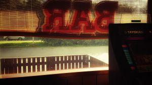 På en bar, persienner och en spelmaskin