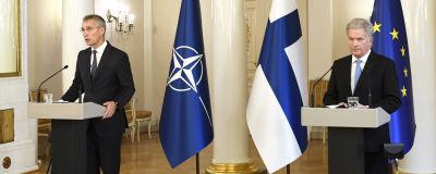 Jens Stoltenberg och Sauli Niinistö står bredvid varandra vid talarpodium och håller tal. I bakgrunden Finlands, Natos och EU:s flagga.