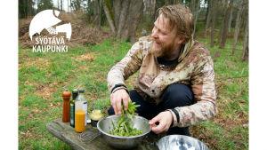 Parrakas mies sekoittaa kyykyssä sormin salaattia kulhossa, joka on puiston penkillä. Taustalla on kaupunkimetsä.  Mies katsoo sivulle ja nauraa.