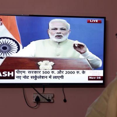 Intialainen mies katsoo pääministeri Modin televisioitua puhetta.