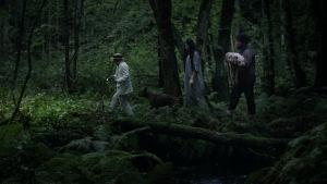 Tre gestalter rör sig genom en mörk skog i filmen Kooko-di Koko-da.