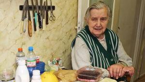 En äldre dam sitter vid sitt köksbord och tittar på de livsmedel hon har fått ta emot
