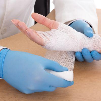 Vårdare lägger bandage på skadad handled.