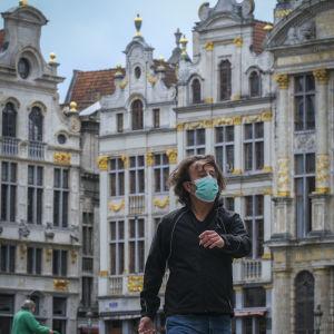 En man med munskydd går över Bryssels historiska torg grand place