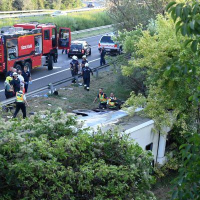 Räddningspersonal runt en buss som kört av vägen i Ungern.